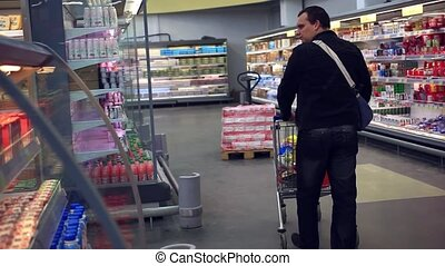 Man with shopping cart with food produces, dairy in...