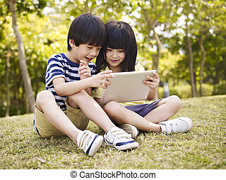 two asian children using tablet outdoors - little asian girl...