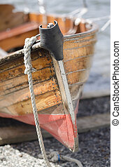 Wooden rowboat - Old wooden rowboat resting on a pebble...