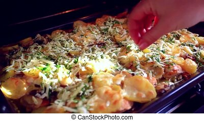Potatoes baking in toaster oven and female hand adds cheese...