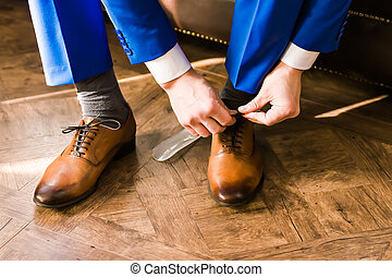 Men's shoes - groom putting his wedding shoes. Hands of...