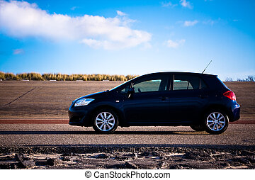 Blue car standing on road. Side with with vibrant sky as...