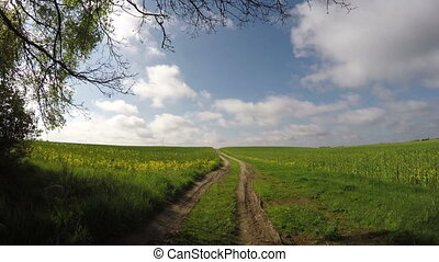 rural gravel road in spring and sky clouds motion Farmland...