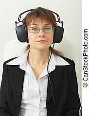 The tired woman the sound technician with professional stereos ear-phones