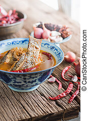 Kaeng Som - sour soup made of tamarind paste with tilapia or...