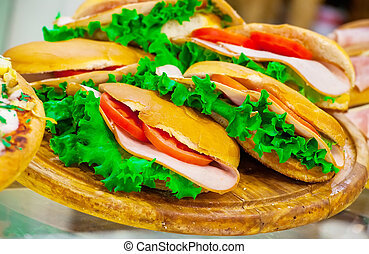 Ham, tomatoes sandwiches and lettuce leaves on a show-window...