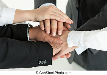 Closeup of business team showing unity with putting their...