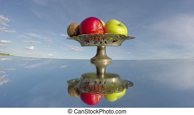 vintage vase with fruits on mirror in space and sky clouds...