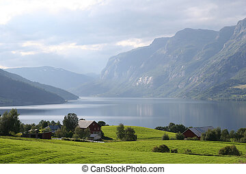 Norwegian landscape - Green sunlit meadows with a lake and...
