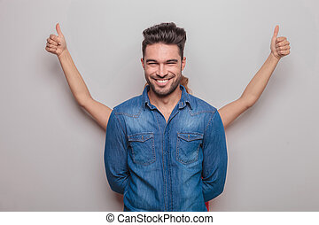 Smiling young man standing with his hand behind