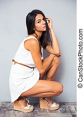 Woman squatting on gray background - Charming young woman...