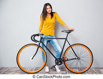 Happy woman standing near bicycle - Full length portrait of...