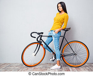 Happy casual woman standing with bicycle - Full length...