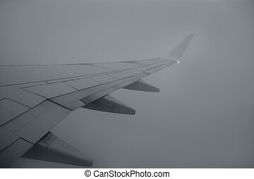 Airplane right wing flying over cloudy gray day sky