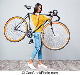 Woman holding bicycle on shoulder - Smiling young woman...