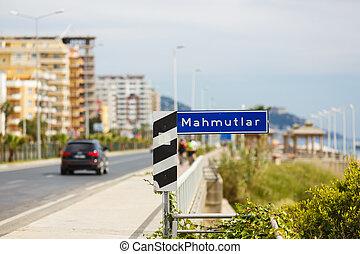 Road sign on seaside street of little town Mahmutlar