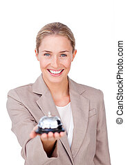 Smiling businesswoman holding a bell isolated on a white...