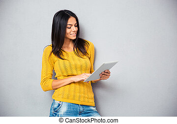 Smiling young woman using tablet computer