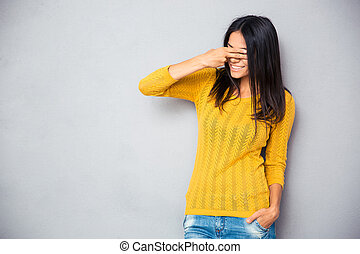 Woman covering her eyes with fingers - Smiling young woman...