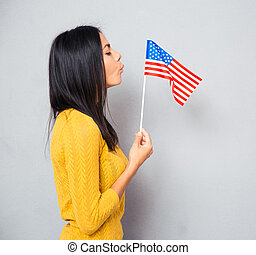 Woman blowing on american flag - Side view portrait of a...