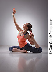Beautiful sporty fit yogi girl practices yoga asana Eka pada...
