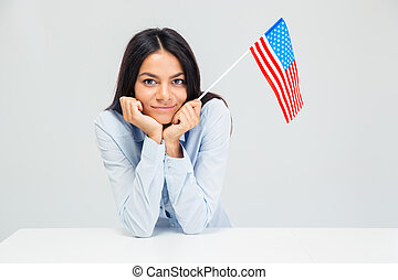 Businesswoman sitting at the table with american flag -...