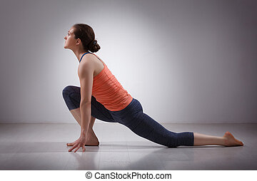 Fit yogini woman practices yoga asana Anjaneyasana -...