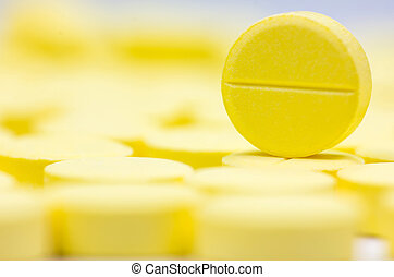 Pharmacy theme, Heap of yellow round medicine tablet antibiotic pills. Shallow DOF
