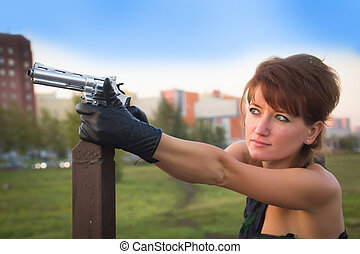 young woman in autumn park holding a gun