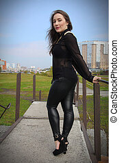 Beautiful girl in black dress and leather pants back view