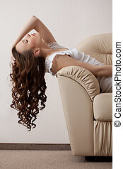 Image of dreaming model reclining on leather sofa