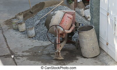 concrete mixer mixes cement solution in street near building...