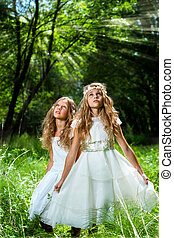 Litte princesses wearing white dresses in woods - Portrait...