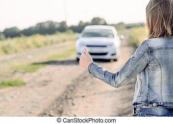 Young woman hitchhiking in the countryside flagging doan an...