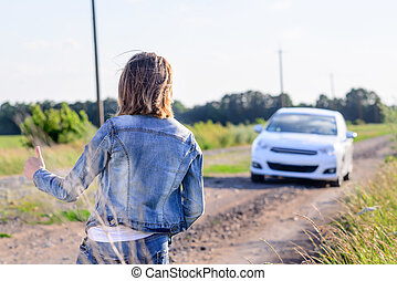 Woman hitchhiking on a rural road - Woman in denim jacket...