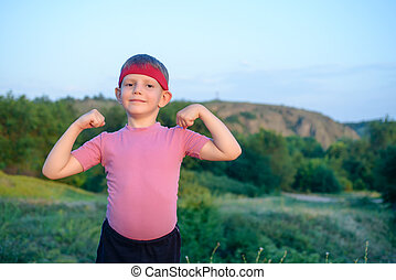 Little boy showing off his biceps - Little boy wearing a red...