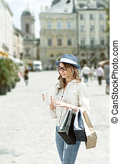 Having a break. - Happy young fashionable woman with bags...