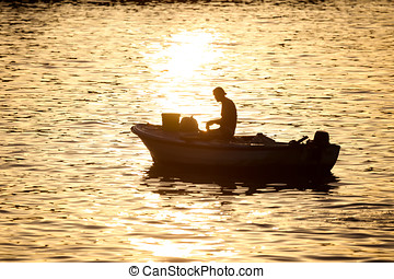 Man in motor boat at sunset - A fisherman in a motor boat...