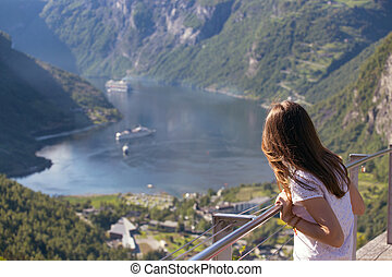 Geirangerfjord - girl looks at Geirangerfjord and mountains...