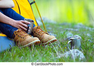 girl hiker in a tent and holding a cup