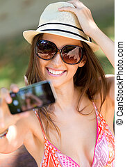 Pretty young girl taking selfies with her smart phone in the...