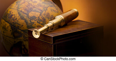 Antique telescope sitting on wooden box with antique map in...