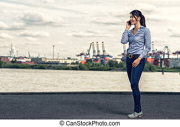 Woman wearing skinny jeans while talking on phone -...