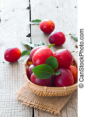 Ripe cherry-plums in the basket over natural wood background...