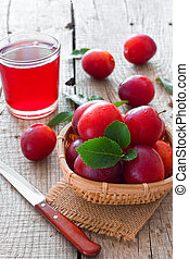 Ripe cherry-plums and glass of juice over natural wood...