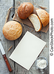 Rustic bread, wheat and flour over natural wood background