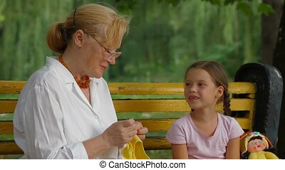 Hand Crafting In A Park - Woman working with a crochet in a...
