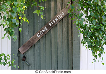 Gone Fishing sign at on old door