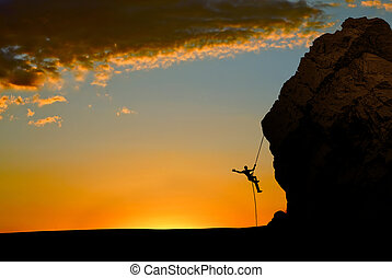 Silhouette of Rock Climber at Sunse - Silhouette of a...