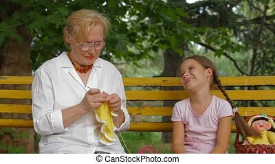 Hand Knitting In A Park - Grandmother talking with her...